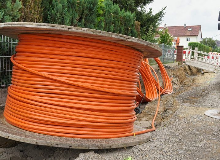 Spool of orange fibre-optic cable on the side of a road waiting to be installed.