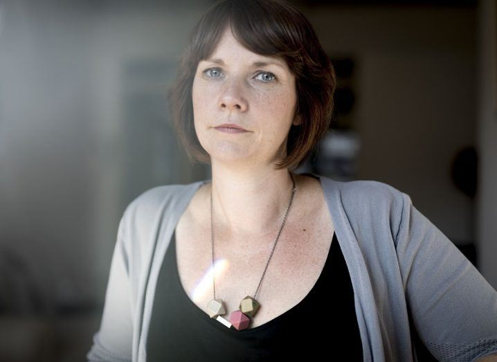 Kate Nolan wearing a grey cardigan and black tank-top against a grey, glass background.