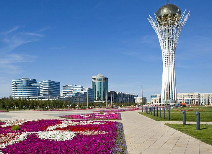 Purple flowers in front of the Bayterek Tower in Astana, Kazakhstan.