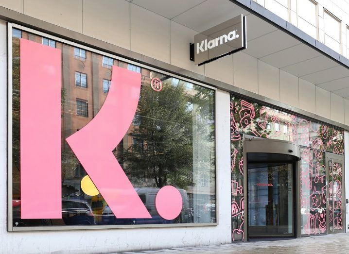 Pink Klarna logo in a window of a company office.