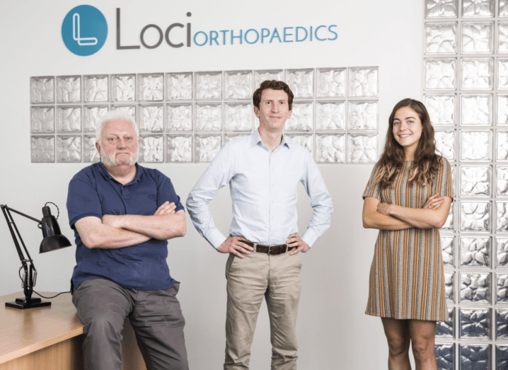 A man in a navy T-shirt sits on a desk with his arms folded, beside a man in a white shirt and slacks and a woman in a beige dress. They are in front of a white wall that reads, 'Loci Orthopaedics'.