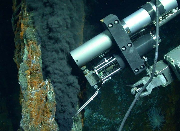 Underwater shot of a thermal vent and a robotic arm collecting methane samples.