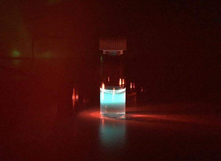 A vial of nanoparticles coloured blue with an infrared light being shone into it against a black background.