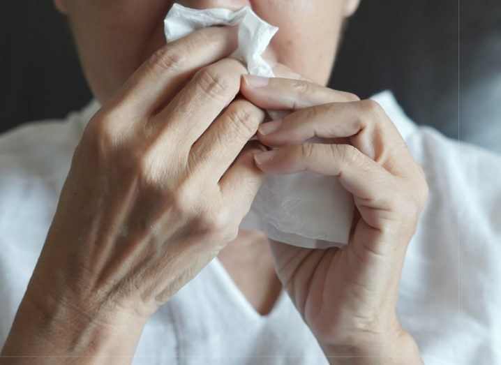 Close-up of a woman in a white T-shirt holding a tissue to her nose.