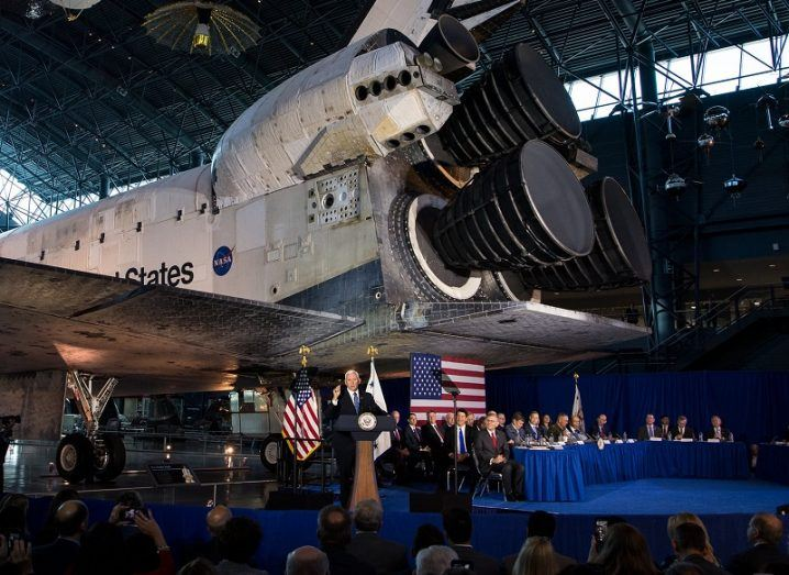 A decommissioned Space Shuttle dwarfing the members of the US National Space Council and audience members.