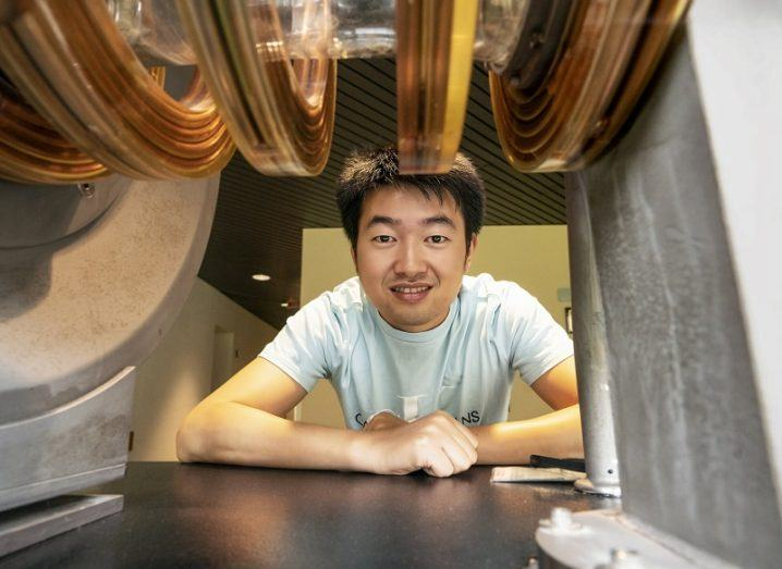 Caoxiang Zhu smiling through a gap with stellarators above him.