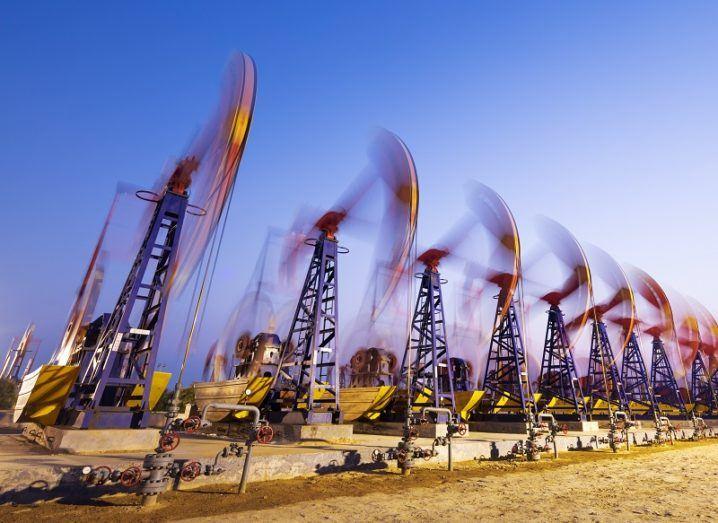 Timelapse shot of oil derricks pumping oil against a dusk background.