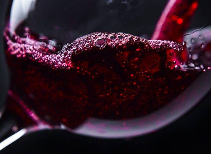 Close-up of red wine being poured into a glass against a black background.