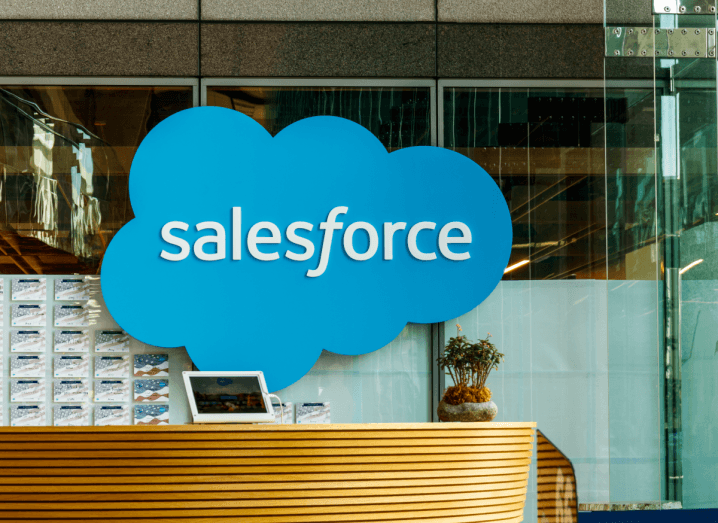 A blue cloud with Salesforce printed on it sits on a glass wall behind a reception desk.