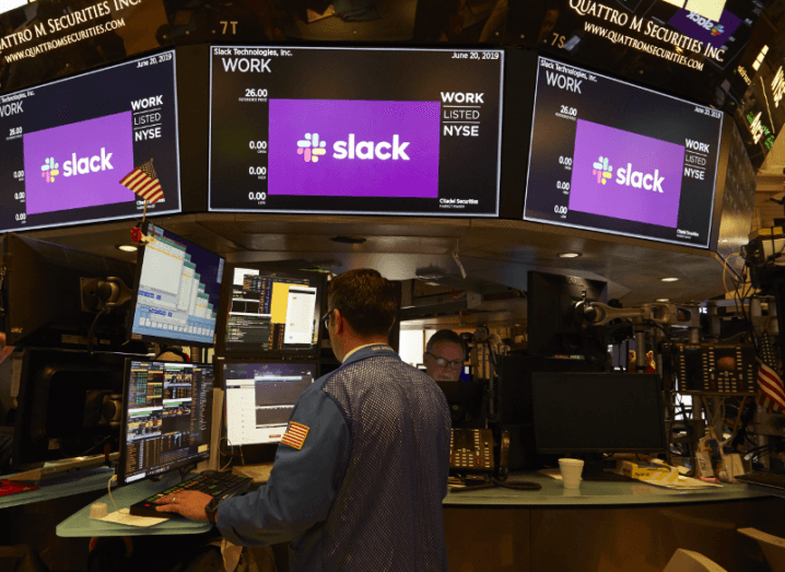 View of Slack Logo at New York Stock Exchange surrounded by screens with stocks and thronged with traders.