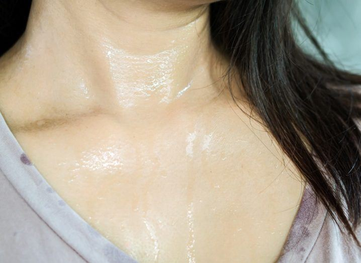 Woman's neck covered in sweat wearing an off-colour pink T-shirt.