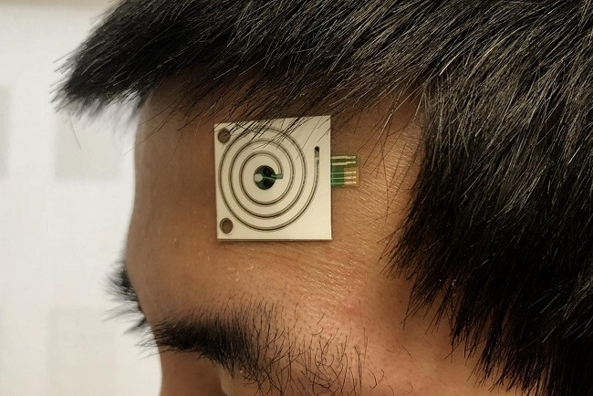 Man wearing the sweat sensor on his forehead.