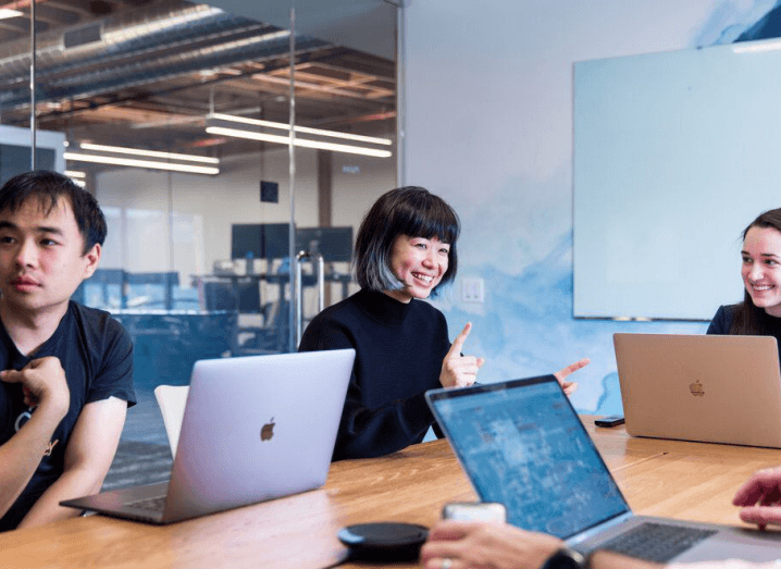 Three young employees at Scale AI sit in a meeting room using MacBooks.