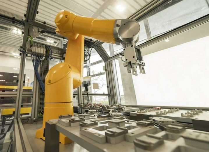 A yellow robotic arm in a factory connected to IoT.