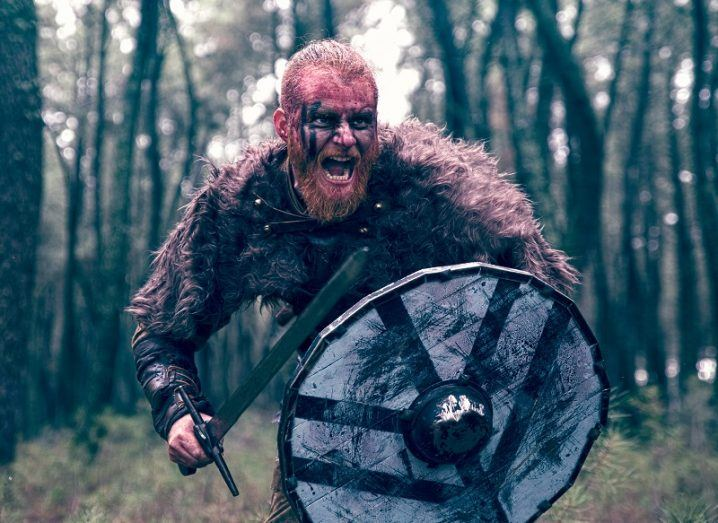 Viking covered in pink facepaint shouting and holding a sword and shield in a forest.