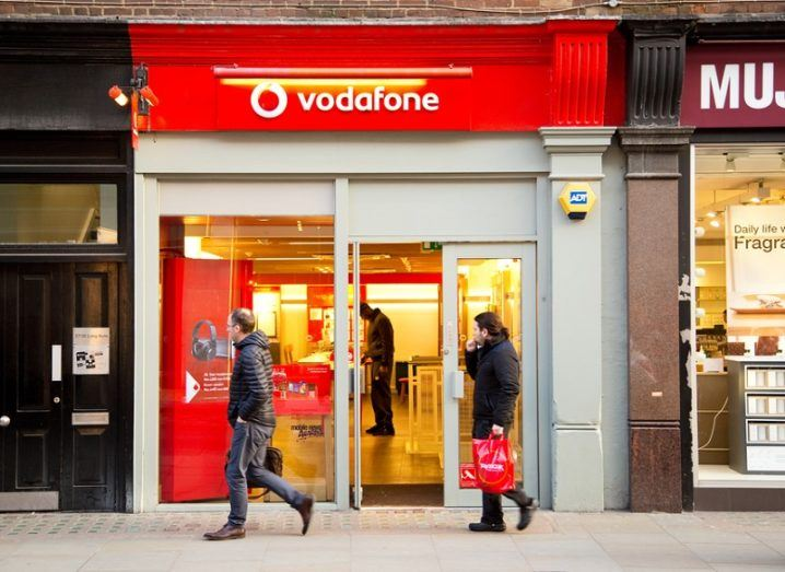 Exterior of a Vodafone store with red branding and people walking past.
