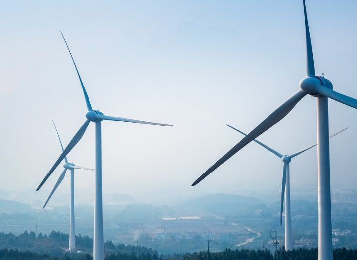 Four wind turbines against a hazy, cloudy background.