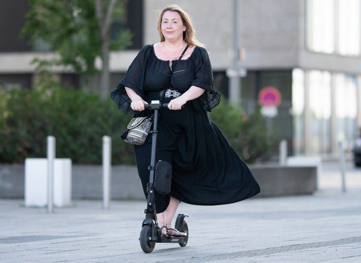 A woman in a black dress riding an e-scooter through a pedestrianised street.