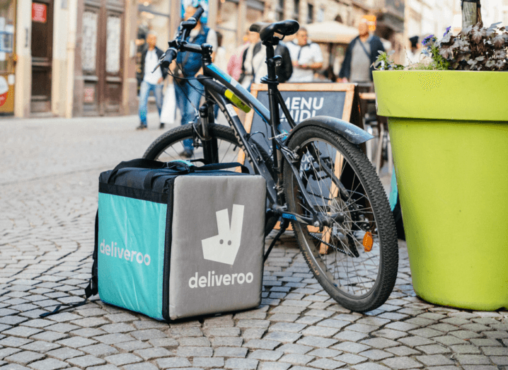 A black mountain bike rests on its stand beside a teal and grey Deliveroo bag, on a cobblestone street.