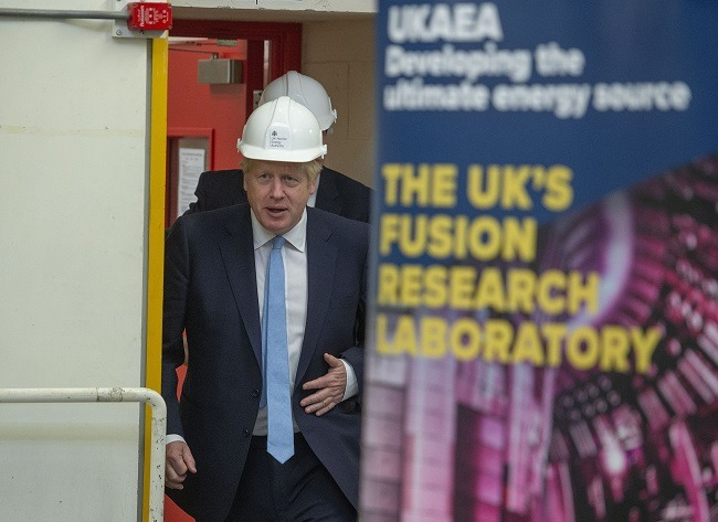 Boris Johnson in a white hardhat walking out a door partly obscured by a poster.