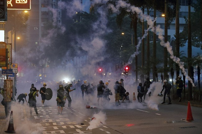 Protest scene with protesters throwing back tear gas at police.