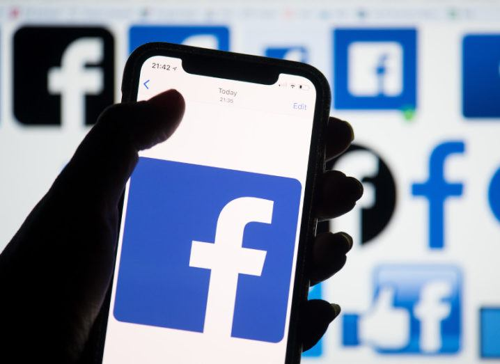 A hand in silhouette holding up a smartphone displaying the Facebook logo against a background of various Facebook logos.
