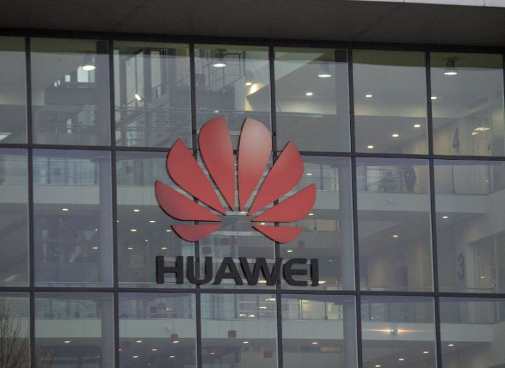 View of glass facade of Huawei building with red lotus logo.