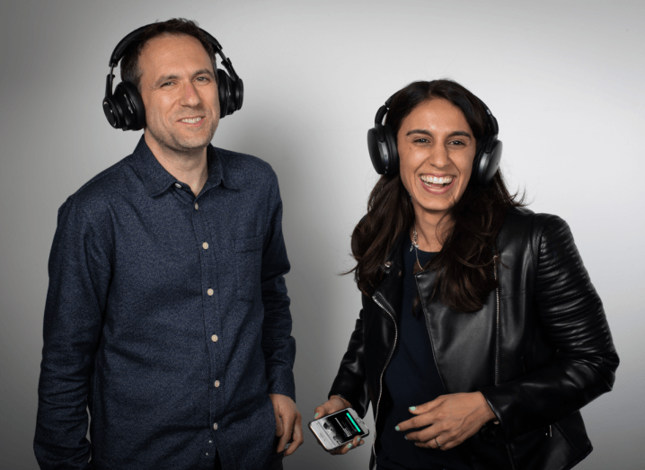 A man wearing headphones and a navy shirt smiles, beside a laughing woman who is also wearing headphones and a black leather jacket.