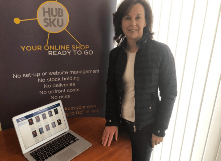 HubSku CEO Freda McEnroe stands in front of a MacBook on a table, beside a sign for her company. She has brown hair and is wearing a black quilted jacket.