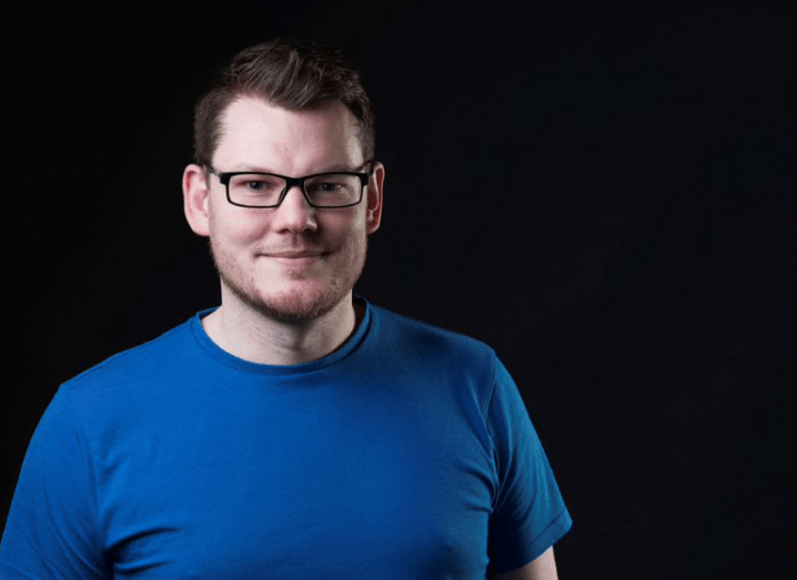Brian D'Arcy standing in front of a black background, wearing a blue T-shirt and a pair of black glasses.