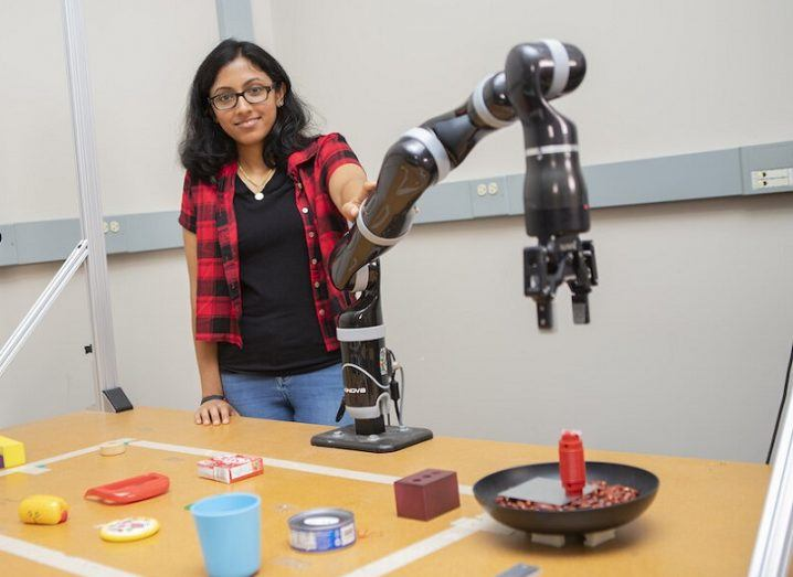 Lakshmi Nair with the 'MacGyver' robot and a range of objects on the table.