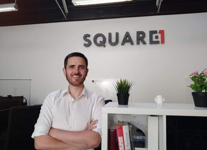 A smiling man in a white shirt with his sleeves rolled up and arms folded stands in an office bearing the Square 1 logo.