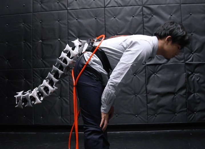 Junichi Nabeshima bending over with the robotic tail sticking out against a black background.
