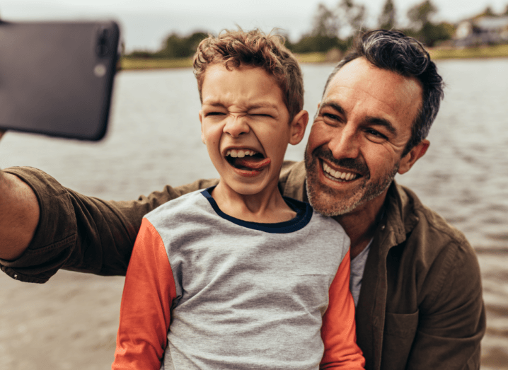 A father and son pose for a selfie together beside a body of water.