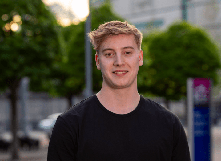 Young blonde man in a black T-shirt standing outside.