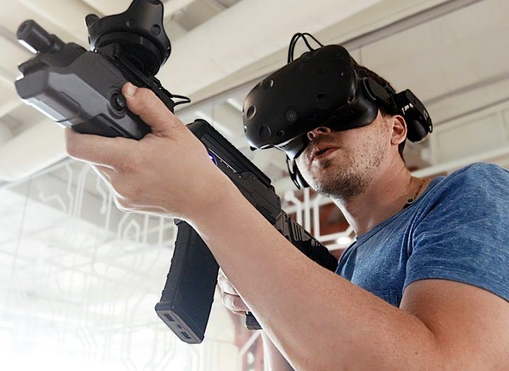 Person wearing a VR headset and holding a VR rifle while playing a video game.