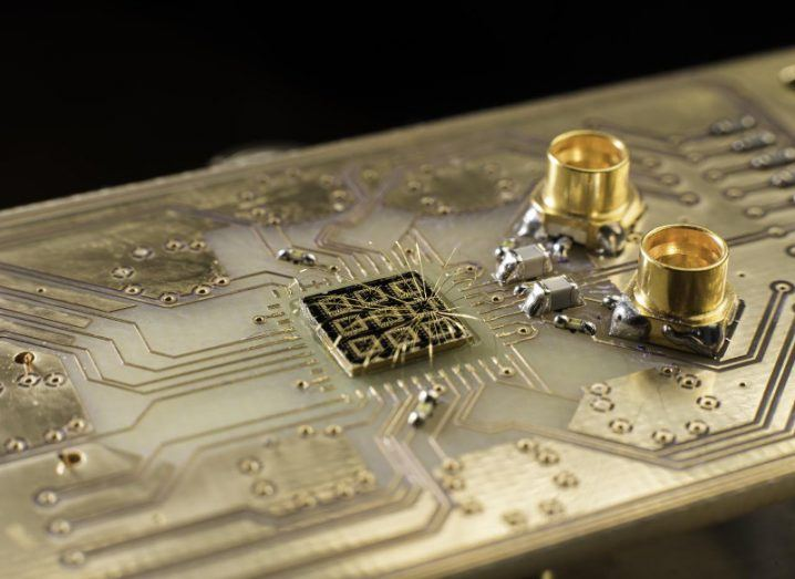 Thin aluminium wires connect the surface of a quantum semiconductor chip to pads on a circuit board.