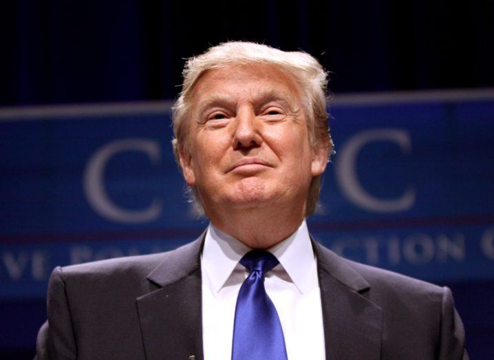 US president Donald Trump in suit and blue tie standing at speaking engagement.