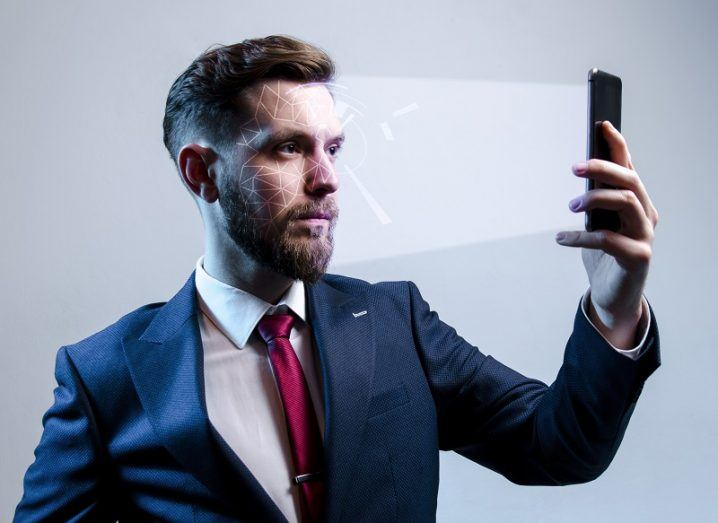 Man in a blue suit, white shirt and red tie pulling a poker face while lying and being scanned by a smartphone.