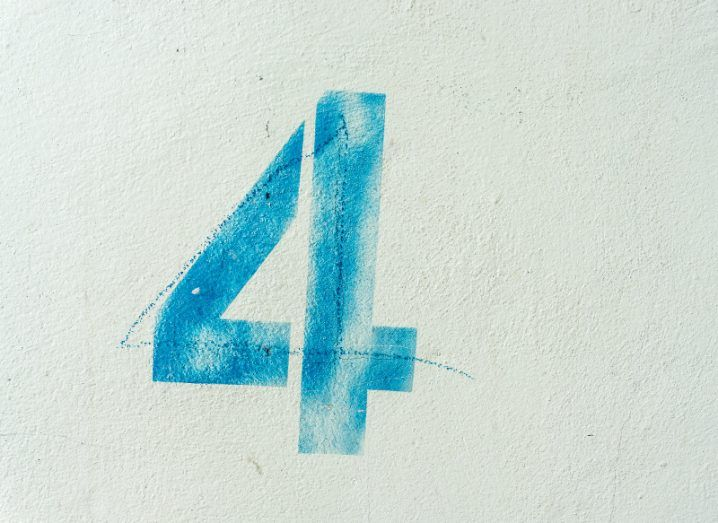 The number four stamped in blue on a white wall, directly over a hand-drawn four.