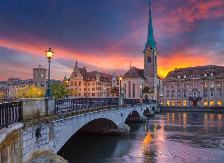 Zurich cityscape seen from across a bridge during a dramatic sunset.