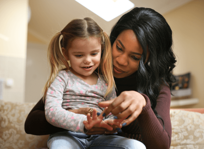 A woman helping a child count on her fingers. The woman has dark hair and is wearing a brown long-sleeved top, the child has blonde hair and is wearing a grey top with pink flowers on it.