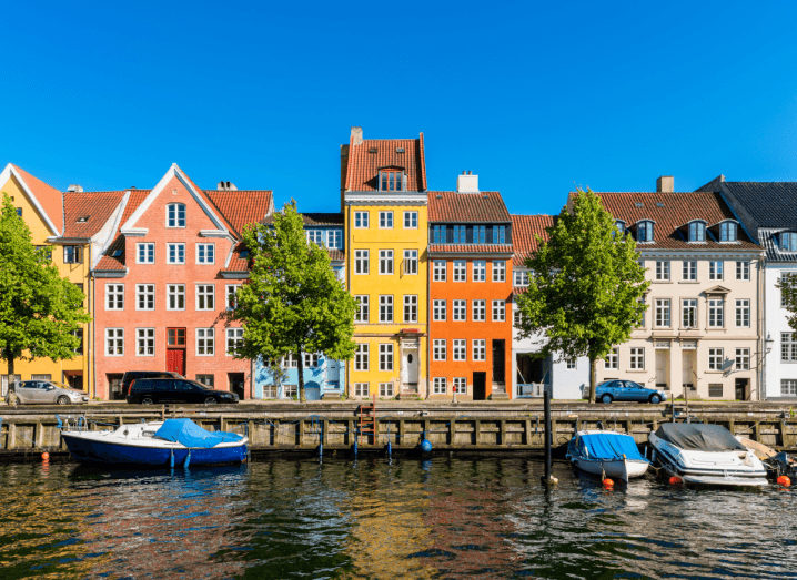 A row of colourful, tall houses at the side of a body of water, where two boats are floating.