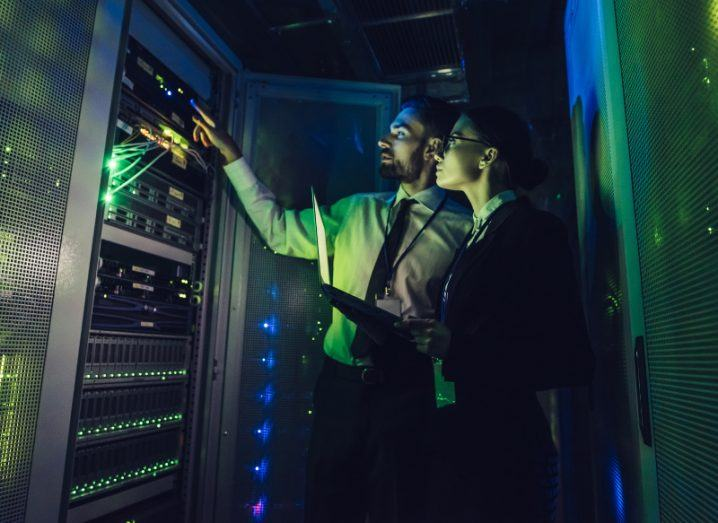 Man and woman looking at a server in a dimly lit data centre.