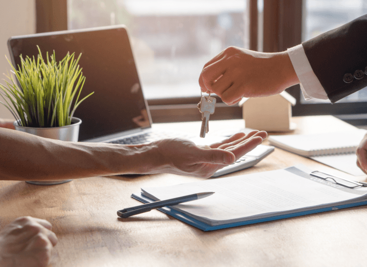 A realtor agent handing over the key of an apartment to a new owner after they signed a lease agreement. The key is exchanged over a desk, which has paperwork, a laptop and an artificial plant on it.