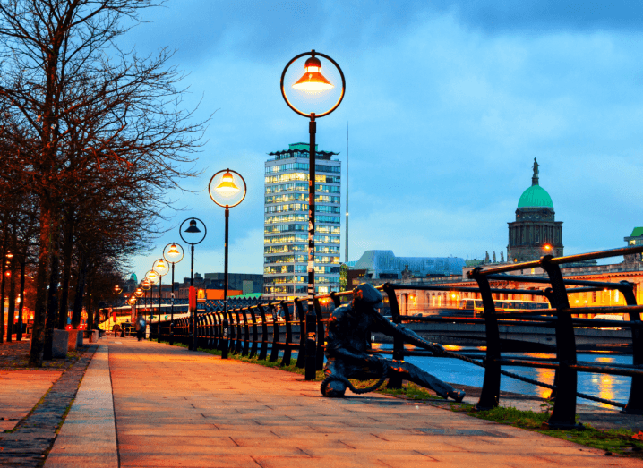 Dublin's quays at dusk in autumn, trees have no leaves and the streetlights are lit along the Liffey leading up to the Sean O'Casey Bridge and Liberty Hall.