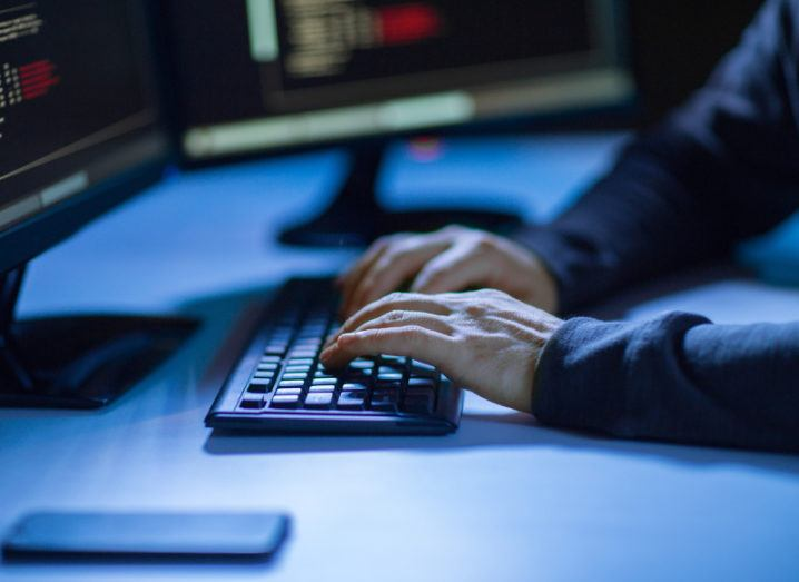 View of man with hands sitting on desktop keyboard representing cyberattacks concept.