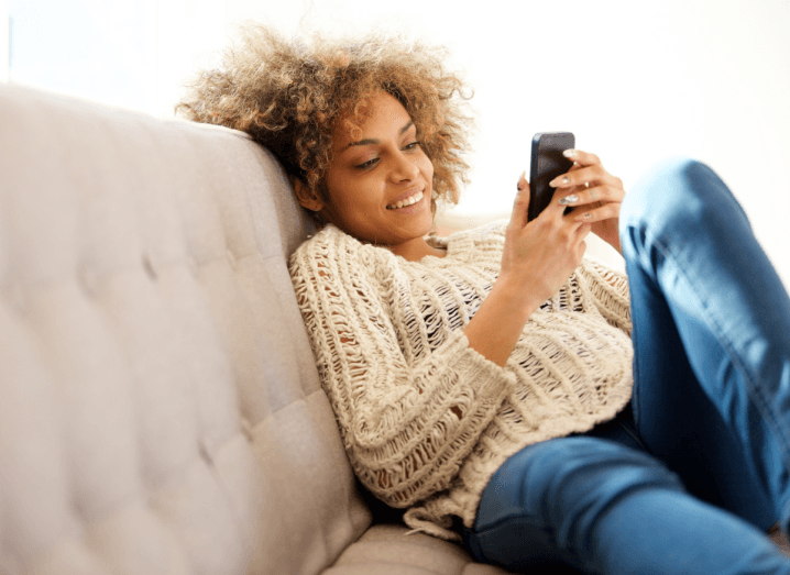 A woman sitting on a beige sofa, wearing a beige jumper and blue jeans, browsing on her mobile phone. She has curly blonde hair.