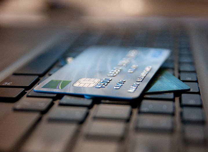 Blue Credit cards on black computer keyboard.