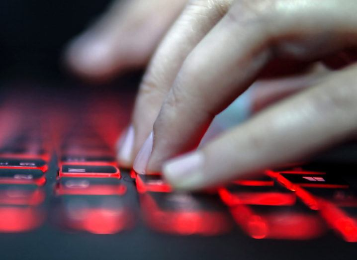 View of hands floating over keyboard backlit with red light.